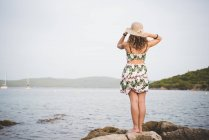 Woman looking out to sea, wearing hat, rear view — Stock Photo