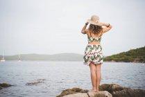 Mulher olhando para o mar, usando chapéu, visão traseira — Fotografia de Stock