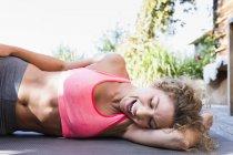 Joven descansando sobre la estera de la yoga en la parte superior de cosecha rosa, risa - foto de stock