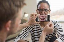 Homem segurando smartphone na frente da boca da mulher — Fotografia de Stock