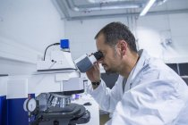 Homme assistant de laboratoire à la recherche dans le gadget de microscope — Photo de stock