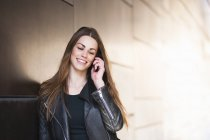 Young woman leaning against wall chatting on smartphone — Stock Photo