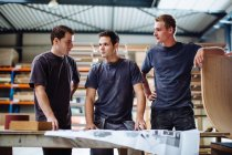 Three young male carpenters having discussion in workshop — Stock Photo