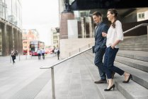 Side view of young businessman and woman chatting while walking down stairway, London, UK — стоковое фото