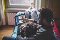 Coppia sdraiata sul divano, utilizzando tablet digitale — Foto stock
