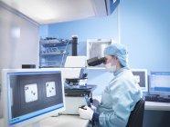 Trabajador electrónico trabajando con microscopio en sala limpia - foto de stock