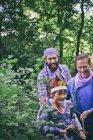 Двое мужчин, захваченных верёвкой мальчиком в лесу — стоковое фото
