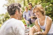 Gruppo di amici maschi e femmine alla festa in giardino — Foto stock