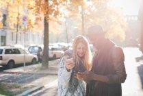 Пара с помощью смартфона на тротуаре — стоковое фото