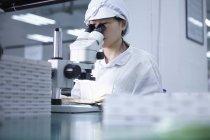 Travailleuse utilisant un microscope dans une usine de haute technologie — Photo de stock