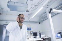 Laborassistentin mit Smartphone im wissenschaftlichen Labor — Stockfoto
