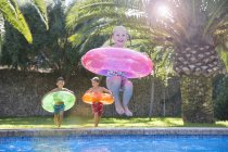 Girl jumping with inflatable ring into garden swimming pool — Stock Photo