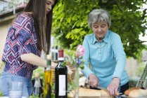 Senior woman cutting bread with granddaughter by outdoor table — Stock Photo