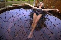 Femme mature allongée en remous eco Retreat — Photo de stock