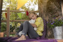 Mädchen mit Stofftier im Baumhaus — Stockfoto