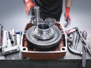 Engineer assembling industrial gearbox in engineering factory, close up — Stock Photo