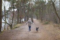 Vista traseira da mulher correndo com seu cachorro na floresta — Fotografia de Stock