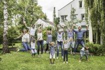 Three generational family jumping in garden — Stock Photo