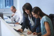 Chers collègues qui regardent la tablette numérique au bureau — Photo de stock