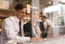 Empresário e empresária trabalhando no laptop no café — Fotografia de Stock