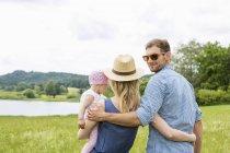 Жінка тримає дитину дочка, людина дивиться через плече — стокове фото