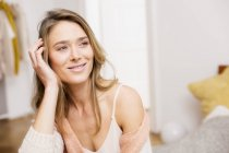 Woman sitting looking sideways from bed with hand on head — Stock Photo