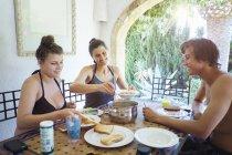 Літня жінка з сином і дочкою їдять обід свято апартамент патіо — стокове фото