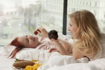Young women having breakfast in bed, Vienna, Austria — Stock Photo