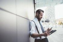 Стильный бизнесмен, использующий смартфон и цифровой планшет вне офиса — стоковое фото