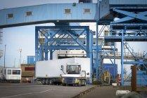 Camion chargeant des conteneurs sur le navire dans le port — Photo de stock