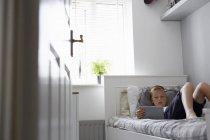 Vista a través de la puerta del niño acostado en la cama mirando hacia abajo en la tableta digital - foto de stock