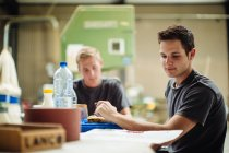 Young male carpenter glancing at blueprint during break in workshop — Stock Photo