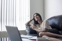 Young woman reclining on sofa — Stock Photo
