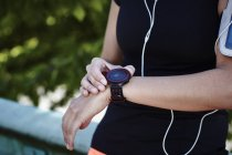 Cropped shot of young female runner setting smartwatch — Stock Photo