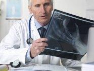 Docteur Regarde un radiographie de main en clinique — Photo de stock