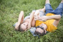 Молода пара лежить на траві в поле, дивлячись на смартфон — стокове фото