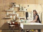 Femme à la table de travail en atelier de main-impression textile — Photo de stock