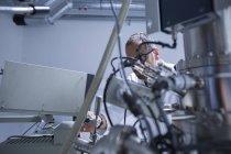 Asistente de laboratorio de microscopía trabajando en equipo - foto de stock