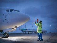 Сотрудник аэропорта направляет самолет на взлетно-посадочную полосу ночью — стоковое фото