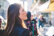 Giovane donna alzando lo sguardo dalla strada della città — Foto stock