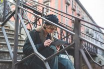 Man using digital tablet on steps, Milan, Italy — Stock Photo