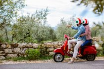 Young couple on moped pointing at olive grove, Florence, Italy — Stock Photo