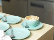 Tazza di caffè e piattini sul tavolo — Foto stock