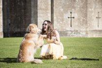 Femme posant avec une tasse de thé et un chien doré au château de Thornbury, South Gloucestershire, Royaume-Uni — Photo de stock