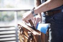 Geschäftsmann steckt Papierkram in Aktentasche — Stockfoto