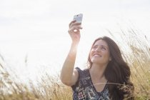 Young woman taking selfie with smartphone in field — Stock Photo