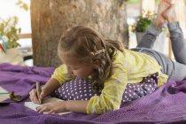 Chica con libro para colorear en la casa del árbol - foto de stock