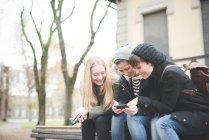 Три сестры, с помощью смартфонов на скамейке в парке — стоковое фото