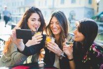 Три женщины позируют для селфи на смартфоне в кафе на берегу — стоковое фото