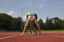 Молодые девушки бегун, наклоняясь вперед на старте гонки трек — стоковое фото